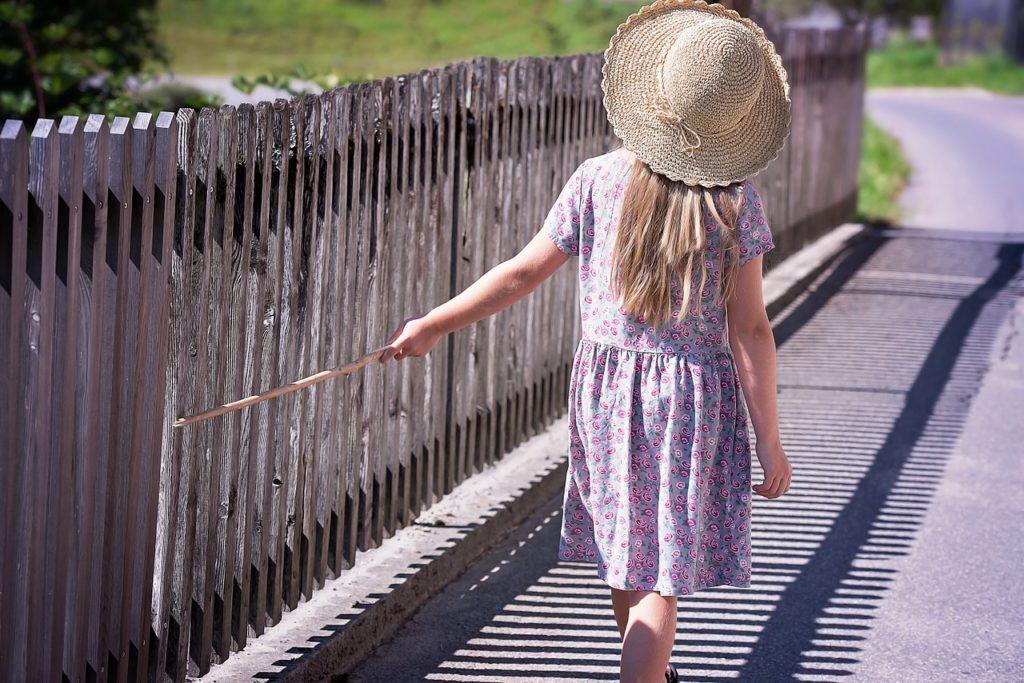 麦わら帽子を被った女の子が散歩している風景