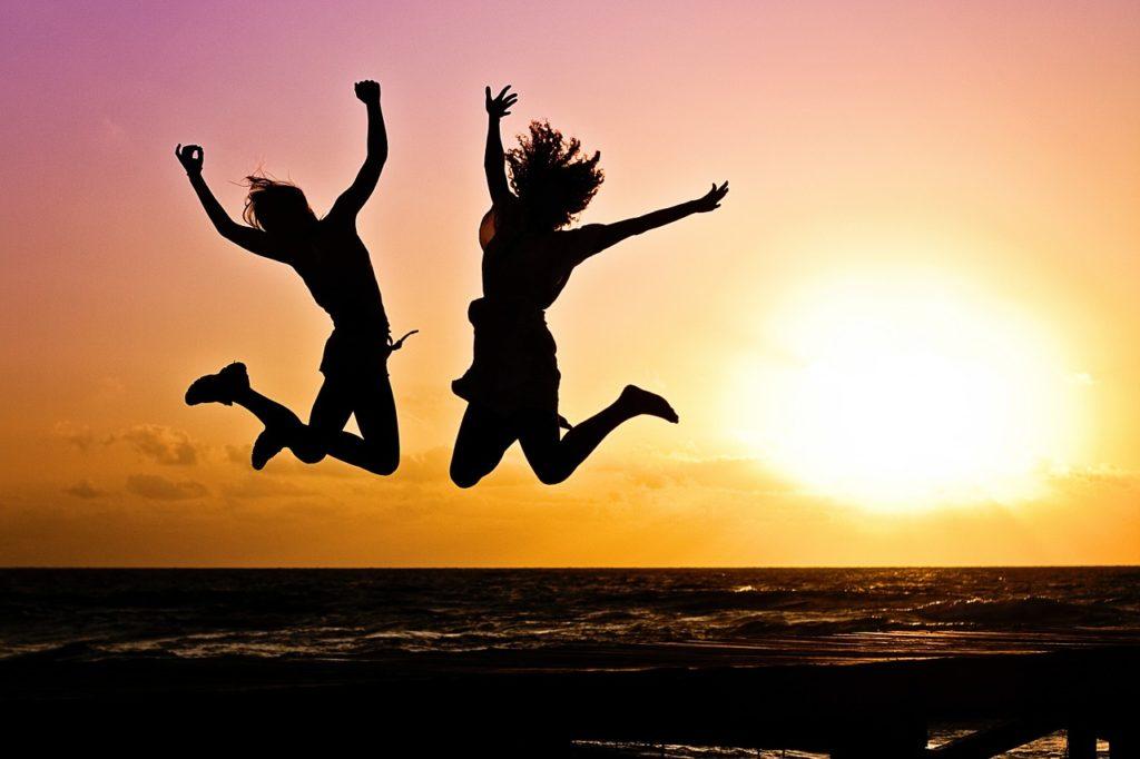 夕日とジャンプする2人の写真