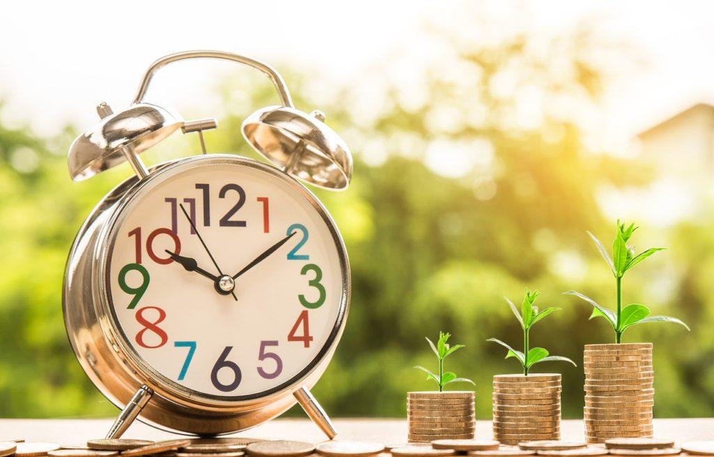 目覚まし時計とコインの写真