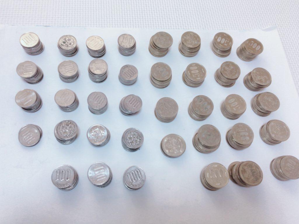 1年間で貯まった100円玉と約10万円分の500円玉の写真