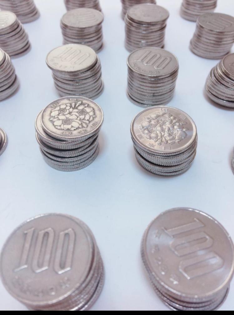 貯金箱に貯めた100円玉の写真
