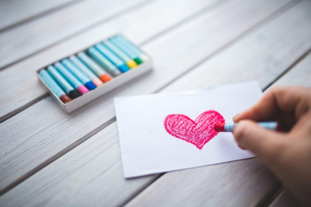 赤色のクレヨンでハートを描いている写真